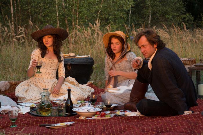 Sommerliche Idylle: Friedrich Schiller (FLORIAN STETTER) mit den beiden Schwestern (HANNAH HERZSPRUNG und HENRIETTE CONFURIUS) bei einem Picknick vor der Ruine ihres Elternhauses